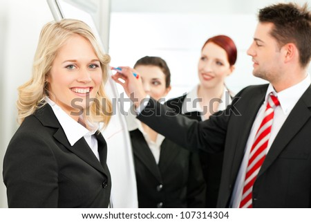 Business - team in an office, a colleague is standing in front of the flipchart, one female colleague is looking in to the camera - stock photo