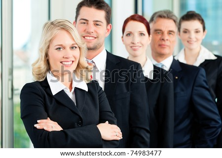 Business - team in an office; five colleagues or professionals in a row - stock photo