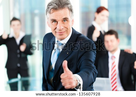 Business - team in an office, the senior executive has the thumb up, focus on thumb - stock photo