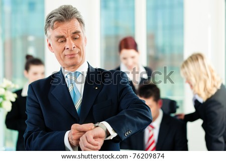 Business - team in an office; the senior executive is checking his watch to hold the deadline - stock photo