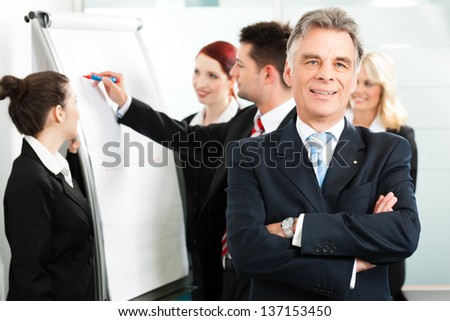 Business - team in an office, the senior executive is standing in front - stock photo