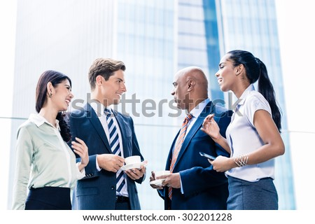 Business team in Asian city having casual coffee, in the background the city skylines with office buildings - stock photo