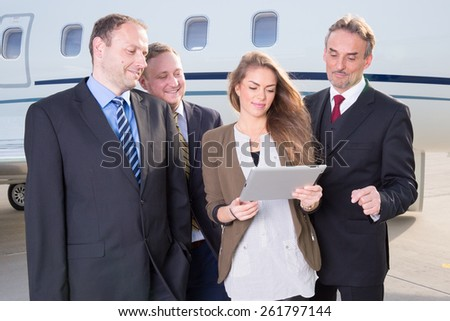 business team in front of corporate jet looking at tablet computer