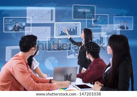 Business team is looking at bar chart on blue world map background - stock photo