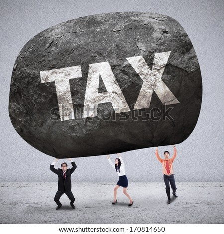Business team lifting the stone of TAX on grey background - stock photo