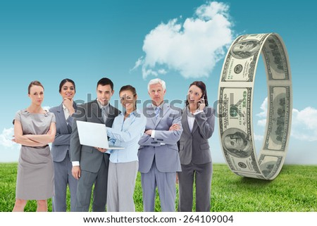 Business team looking at camera against field and sky - stock photo