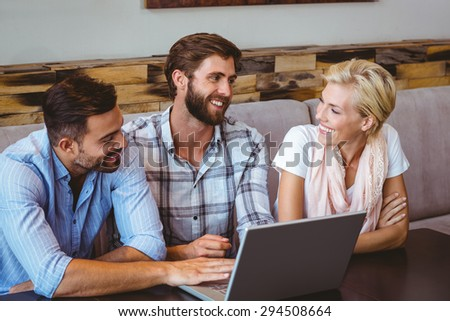 Business team looking at laptop in the cafe - stock photo