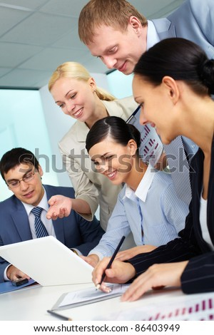 Business team looking at laptop screen - stock photo