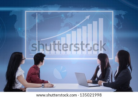 Business team looking at profit bar chart on touchscreen - stock photo