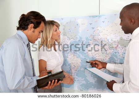 Business team looking at world map - stock photo