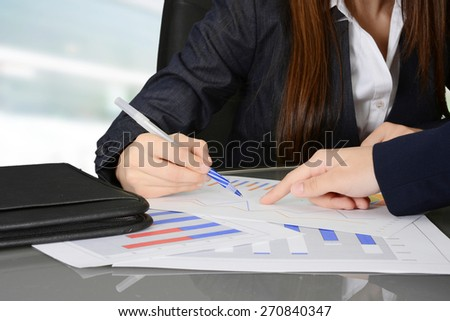Business team looking over and analyzing data charts