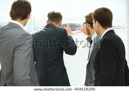 Business team looking through the office window, view from the back - stock photo
