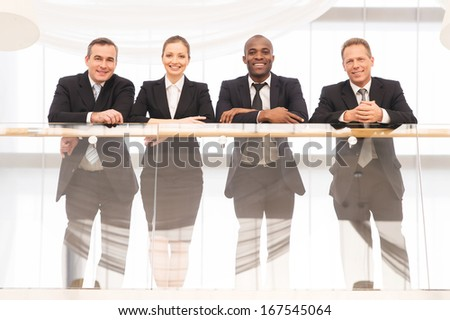 Business team. Low angle view of four confident business people standing close to each other and smiling at camera - stock photo