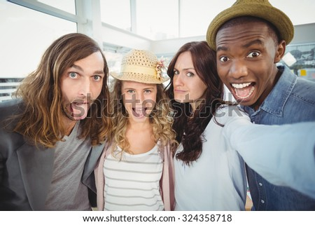 Business team making face while taking self portrait at office - stock photo