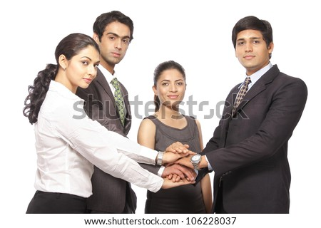 Business team making of pile of hands showing unity over white background