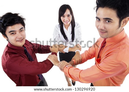Business team making unity gestures by holding their arms on white background - stock photo