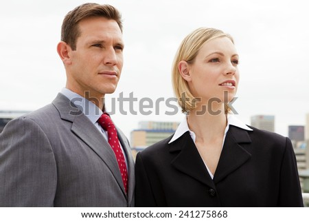 Business team - Man and woman looking away - they are both in their thirties. - stock photo