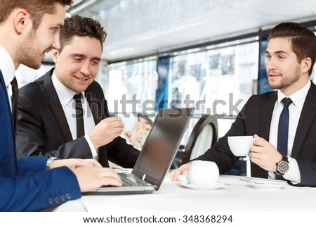 Business team meeting. Portrait of three businessmen wearing formal suits having a business lunch together discussing work - stock photo