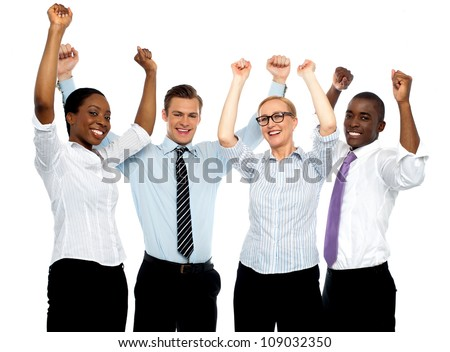 Business team of four celebrating success with arms raised isolated against white background