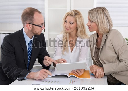 Business team of man and woman sitting around desk in a meeting looking at tablet. - stock photo
