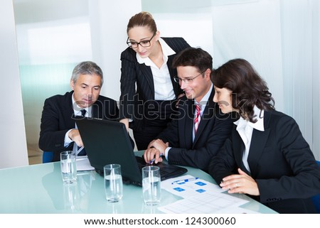 Business team of professional men and women have a meeting gathered around a laptop computer surrounded by literature