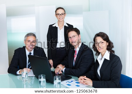 Business team of professional men and women have a meeting gathered around a laptop computer surrounded by literature - stock photo