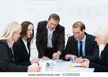 Business team of successful young men and women in a meeting gathered around a table discussing paperwork - stock photo