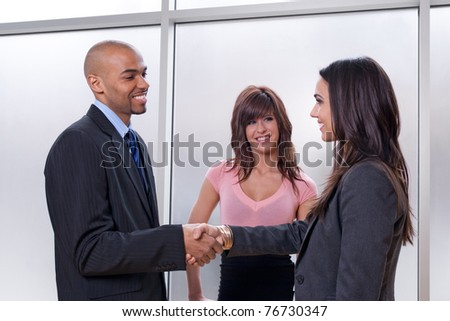Business team of three, man and woman shaking hands. - stock photo