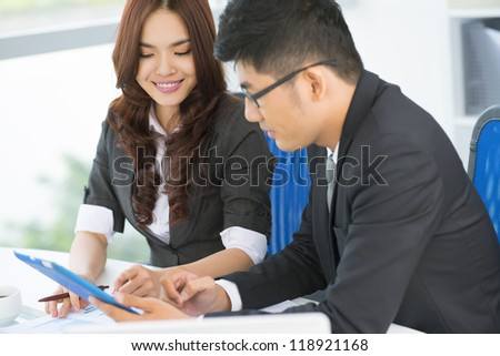 Business team of two making use of modern technology to solve business problems - stock photo