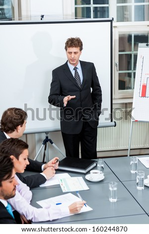 business team on table in office conference seminar presentation - stock photo