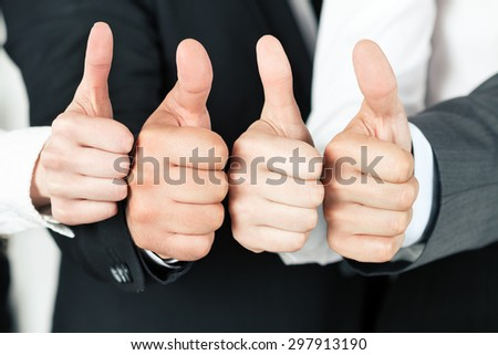 Business team pointing up their thumbs. of different business people pointing up. Concept of success and teamwork. - stock photo