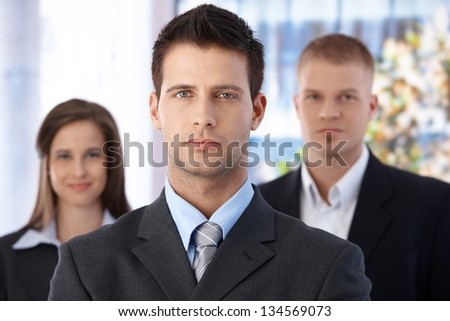 Business team portrait, focus on smart and handsome businessman, coworkers in background.