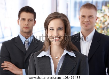 Business team portrait, happy confident businesswoman in focus, businessmen in background.