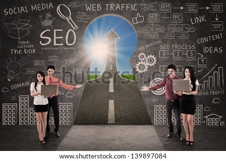 Business team present SEO success road concept through a keyhole - stock photo