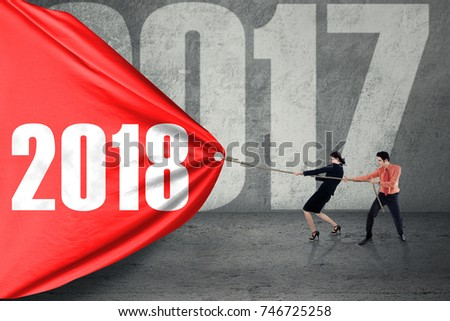 Business team pulling a red banner with numbers 2018, symbolic of business effort for 2018