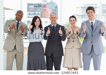 Business team putting their thumbs up to show a success