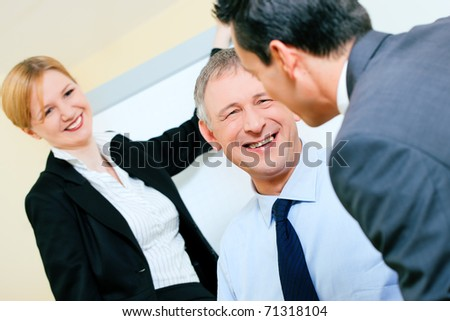 Business team receiving a presentation held by a female co-worker standing in front of a flipchart - stock photo