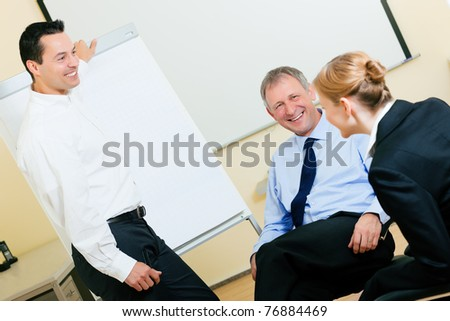 Business team receiving a presentation held by a male co-worker standing in front of a flipchart - stock photo