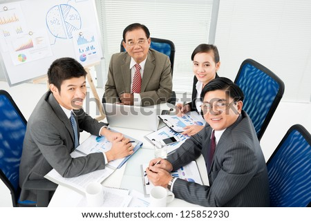 Business team seated at table and looking at camera - stock photo