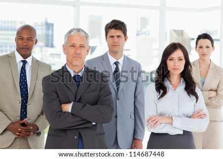 Business team seriously looking at the camera while standing in front of a window - stock photo