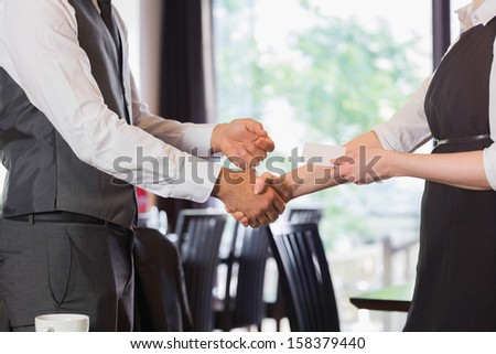 Business team shaking hands and swapping card in a cafe - stock photo