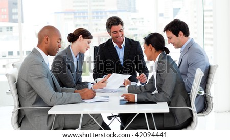 Business team showing ethnic diversity in a meeting smiling at the camera