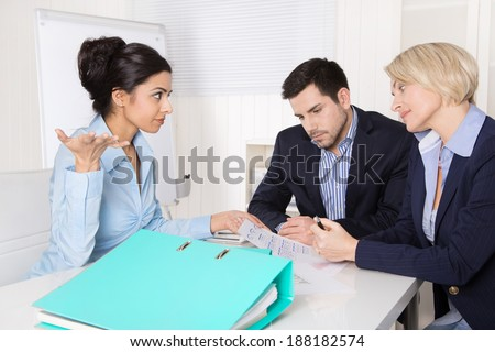 Business team sitting around a table in a meeting talking together. - stock photo