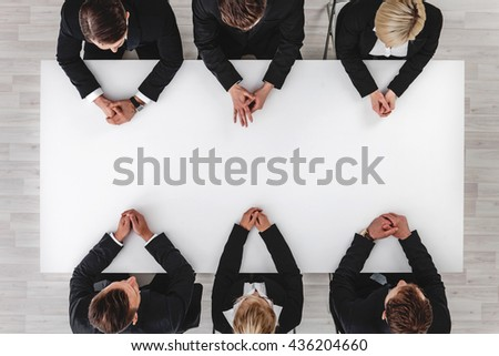 Business team sitting around white table, white copy space