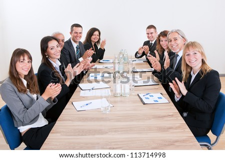 Business Team Sitting At Table And Applauding During Presentation
