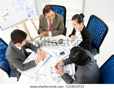 Business team sitting at table and looking at colleague