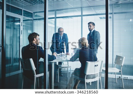 Business team sitting at the table and having meeting - stock photo
