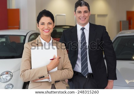 Business team smiling at camera at new car showroom