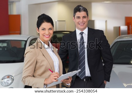 Business team smiling at camera at new car showroom - stock photo