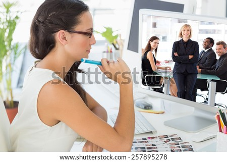 Business team smiling at the camera in a meeting against focused young editor working at her desk - stock photo